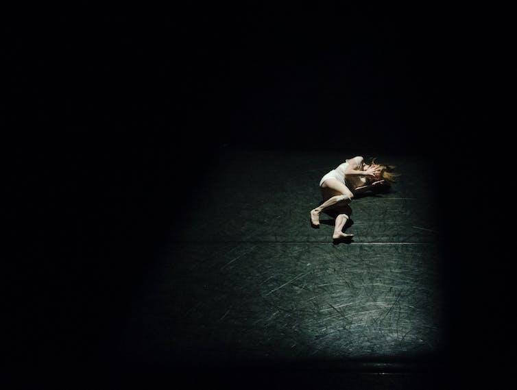 Woman lies in spotlight onstage
