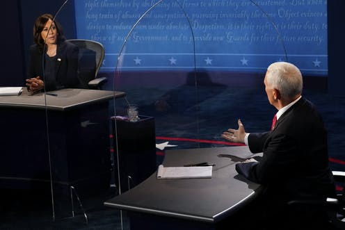 Harris and Pence face each other on the debate stage through plexiglass barrier.