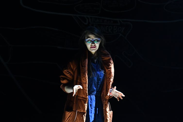 Performer in spotlight wearing fur coat.