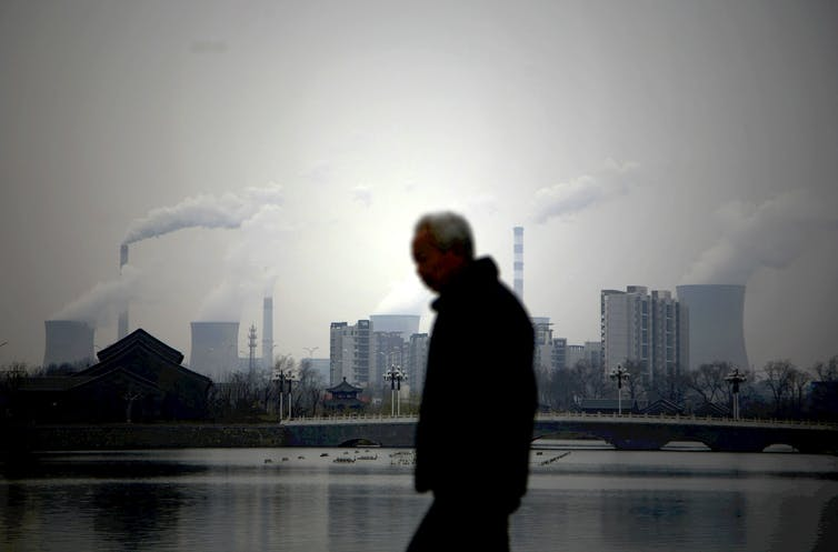 A man walking against an industrial skyline