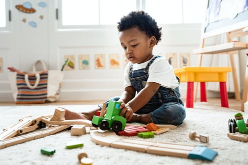 A young boy plays with wooden toys on the floor.