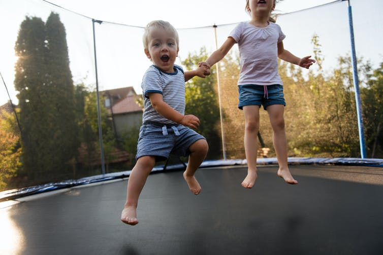 Two young children jumping on a trampoline.