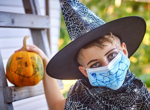 A young boy wearing a black witches hat with a surgical mask on his face holding a painted Halloween pumpkin