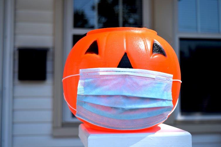 A Halloween pumpkin wearing a surgical mask