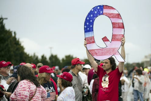A man holds up a large letter Q at a protest.