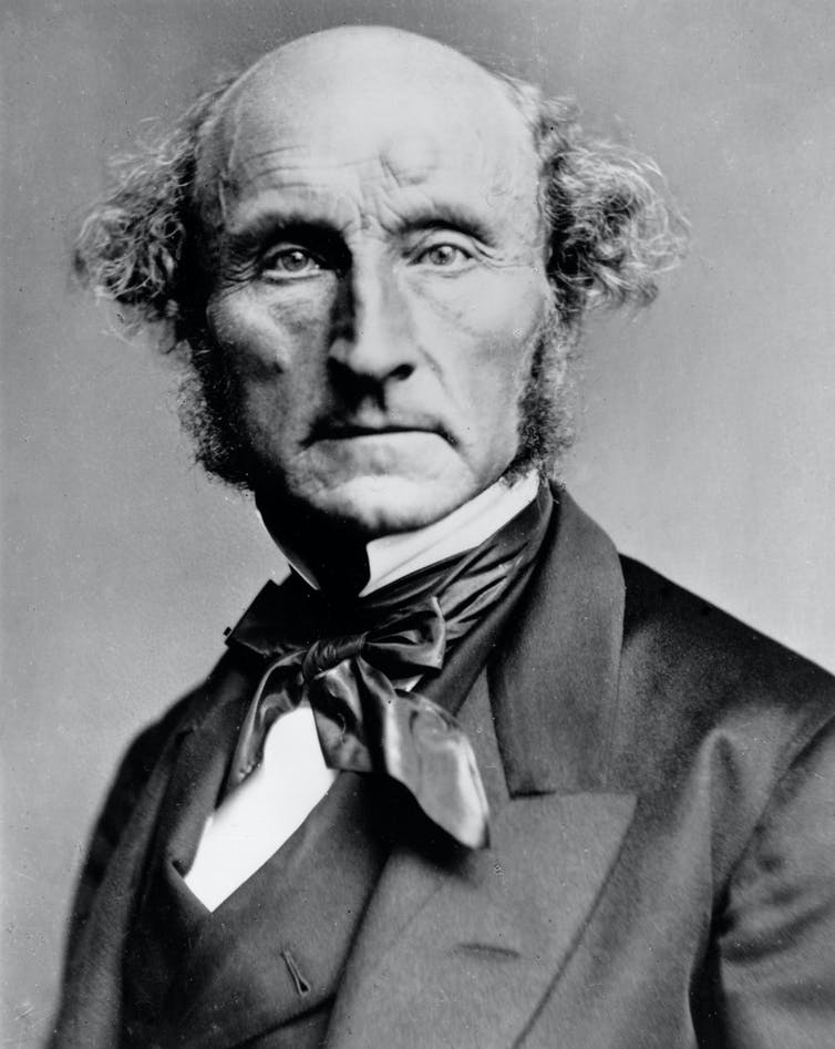 A black-and-white photograph of a bald middle-aged man in late 19th-century dress (John Stuart Mill).k