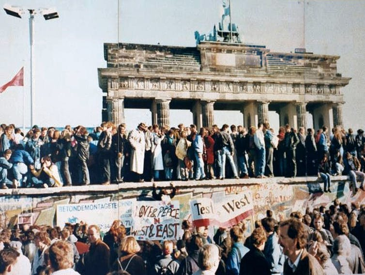 Crowds stand atop the Berlin Wall.
