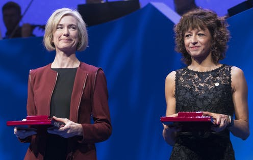 Jennifer Doudna and Emmanuelle Charpentier in smart dress holding red prize boxes.