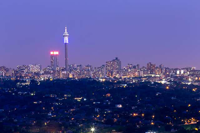 The skyline of Johannesburg at night with two prominent towers against a moody sky.