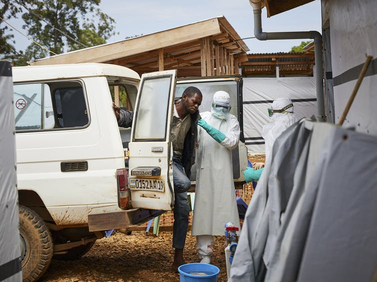 Health workers in the DRC assist a man potentially infected with Ebola.