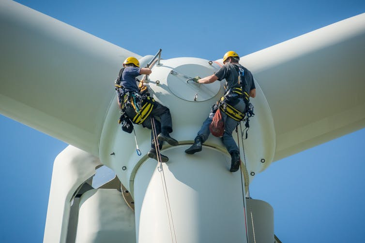 Two engineers in harnesses attend to a wind turbine.