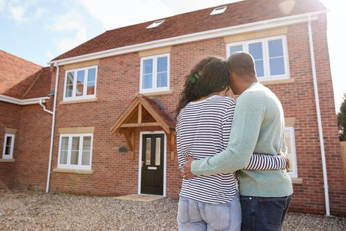 Couple embracing looking at new house