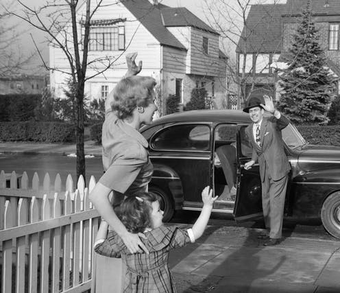 Mother and child waving goodbye to father who is heading to work in 1950's suburb.