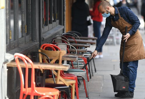 A man wearing a mask cleans tables at a cafe