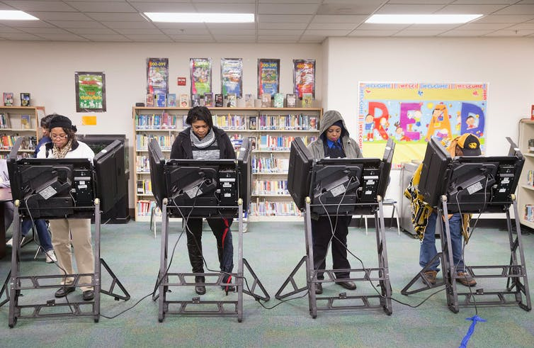 Four voters who are Black casting ballots.