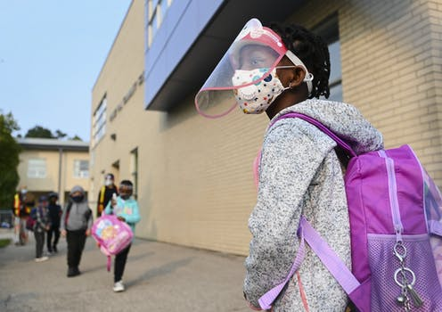 A young girl wears a mask and face shield as she waits in line for her kindergarten class to enter her school.