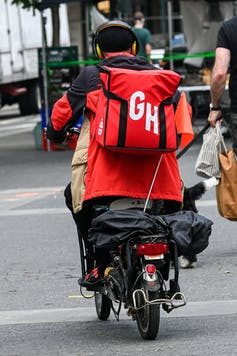 A Grubhub delivery man speeds off on his electric bike to make a delivery on May 29 in New York City.