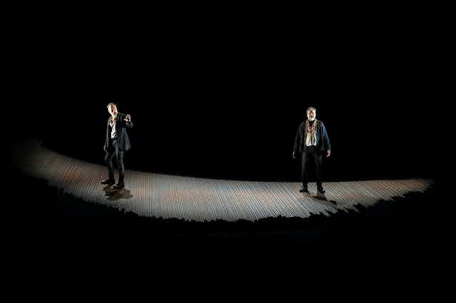 Two men onstage in light with dark surrounds.