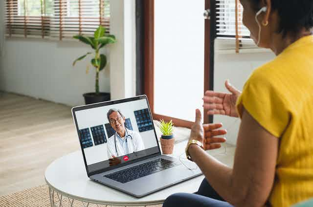 A woman speaks to a doctor on her laptop.