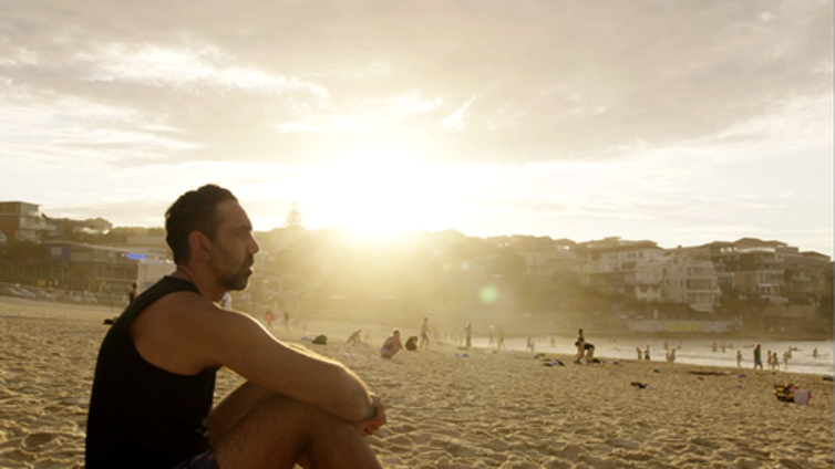 Film still: Adam Goodes on a beach