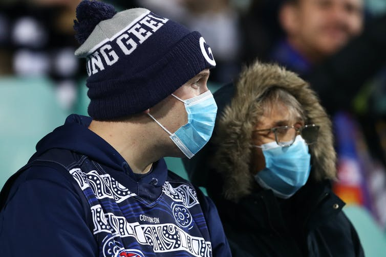 Two people watching a sports match wearing masks