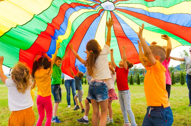 Children playing outside under a colourful parachute
