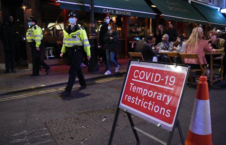Police in London wearing masks patrol a busy street in Soho.