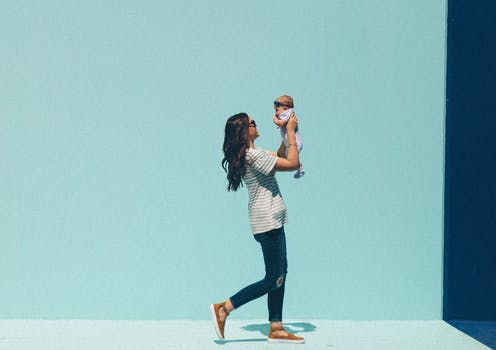 A woman walks with a baby.