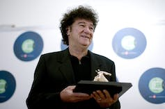 A man with dark curly hair dressed in black holds a trophy.