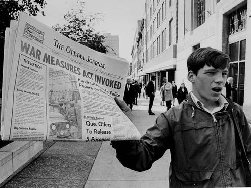 A boy holds up a newspaper with the banner headline War Measures Act invoked.