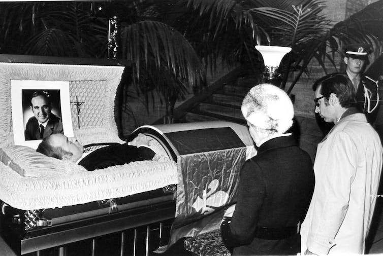 Pierre Laporte's open casket, with two people kneeling in front of it.