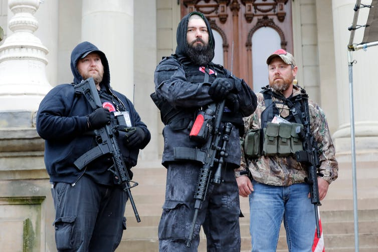 Armed men stand on the steps of the Michigan capitol building.