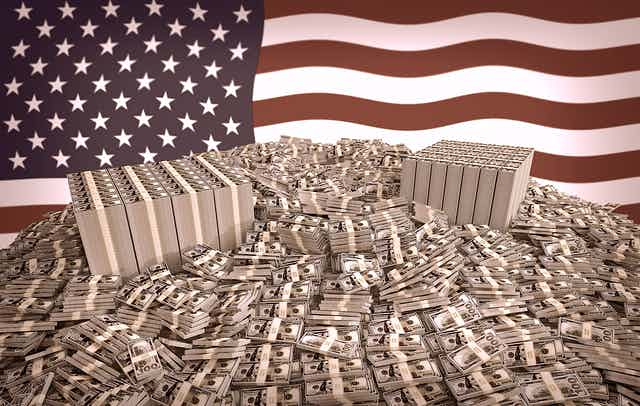 Stacks of dollar bills in front of an American flag