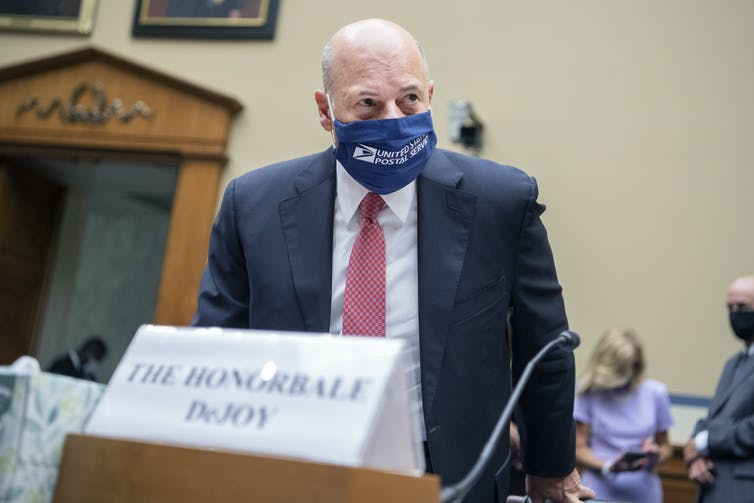 DeJoy arrives speak in the House of Representatives wearing a USPS face mask