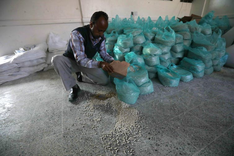 Man puts food aid into plastic bags.