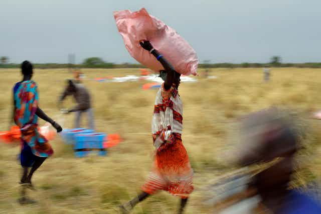 Villagers pick up sacks of air-dropped food .