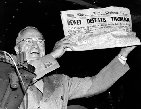 "Harry Truman holding a newspaper with the headline ""DEWEY DEFEATS TRUMAN"""