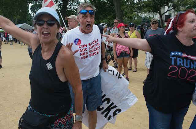"""A Trump supporter's t-shirt says """"CNN SUCKS, ABC SUCKS, NBC SUCKS, CBS SUCKS."""""""