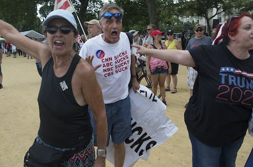 "A Trump supporter's t-shirt says ""CNN SUCKS, ABC SUCKS, NBC SUCKS, CBS SUCKS."""