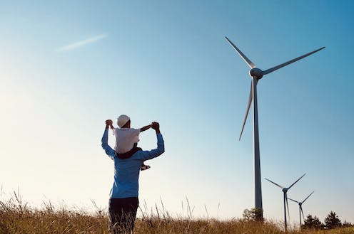 Man and child look at wind turbines