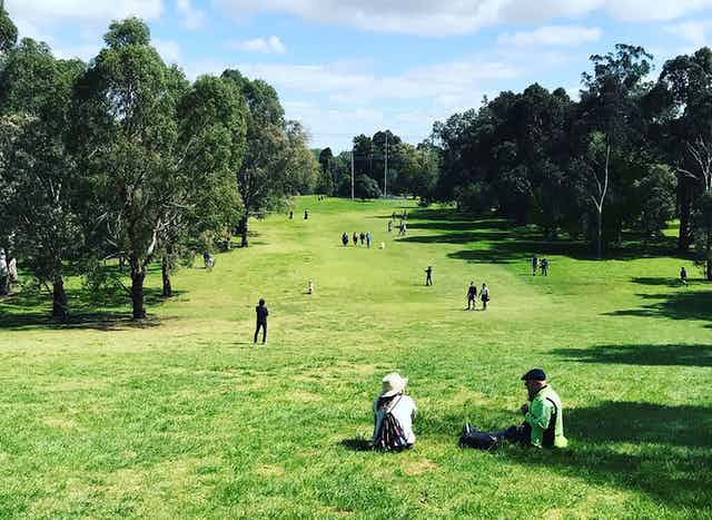 people sitting and walking on golf course