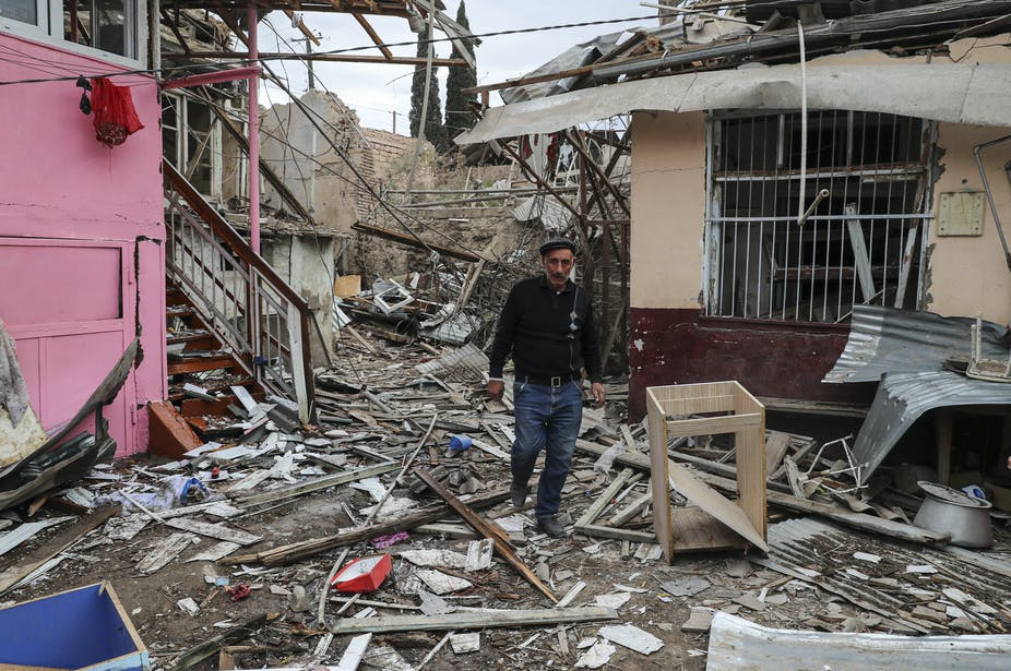 A man walks in between damaged houses.