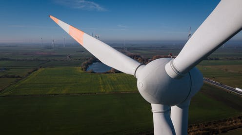 A close-up view of a wind turbine with the countryside behind it.