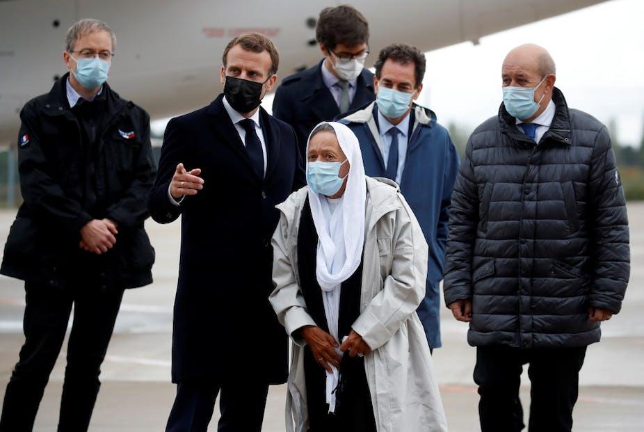 Le président français Emmanuel Macron accueille Sophie Petronin aux côtés du ministre français des affaires européennes et étrangères Jean-Yves Le Drian