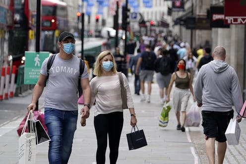 Couple wearing masks on busy shopping street