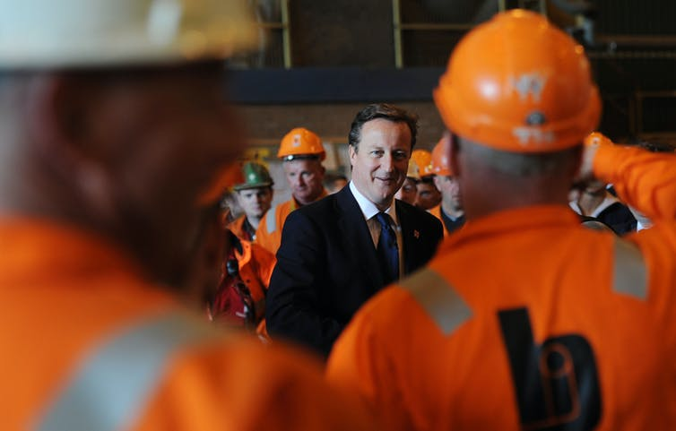 Prime Minister David Cameron meets workers in orange uniforms and hard hats in 2012.
