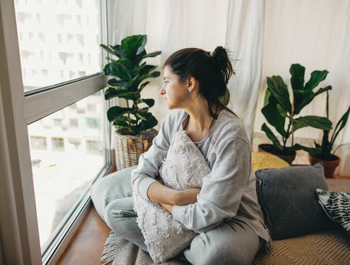 Sad woman looking out of window of apartment