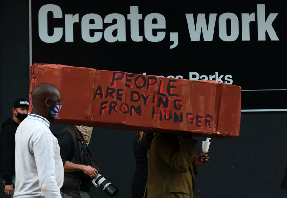 """Protestors carrying a make-shift coffin with the words: """"people are dying from hunger""""."""