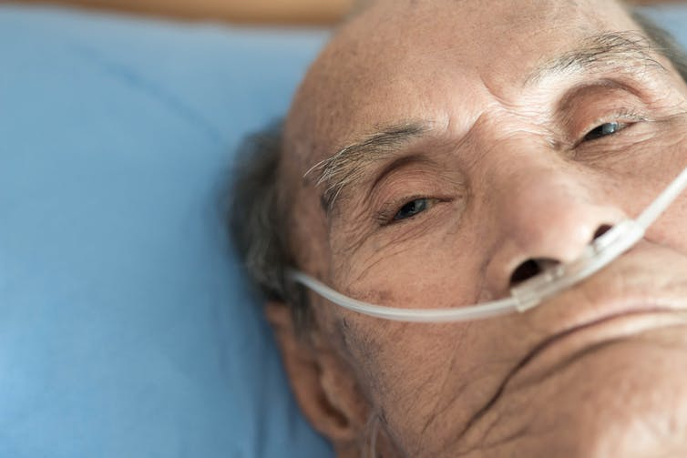 An elderly man receiving supplemental oxygen.