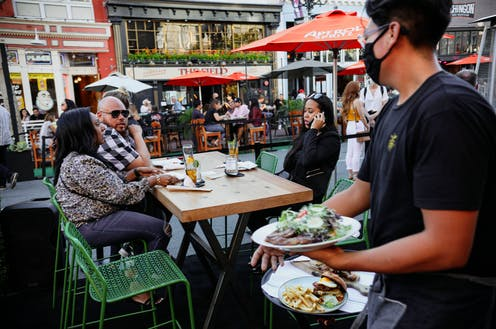 People eating outdoors at a restaurant in San Diego.